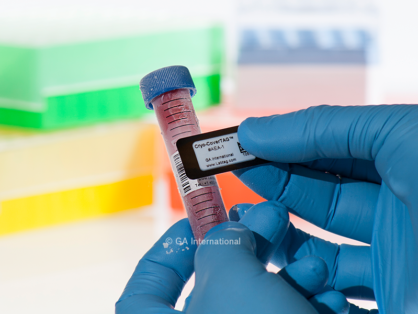 Gloved hands applying a Cryo-CoverTAG blackout cryogenic label, printed with text and a 2D barcode, over an existing label on a frozen 15 ml tube.