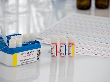 Eine offene Kryo-Box und 3-Kryo-Fläschchen, die mit kryogenen Inkjet-Etiketten auf einem Labortisch beschriftet sind, vor bedruckten Blättern mit Cryo-JetTAG-Etiketten.