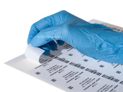 A gloved hand peeling an autoclave-resistant laser label from a sheet of autoclave laser labels printed with alphanumeric text and barcodes.