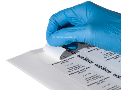 A gloved hand peeling an autoclave-resistant laser label from a sheet of autoclave laser labels printed with alphanumeric text and 1D barcodes.