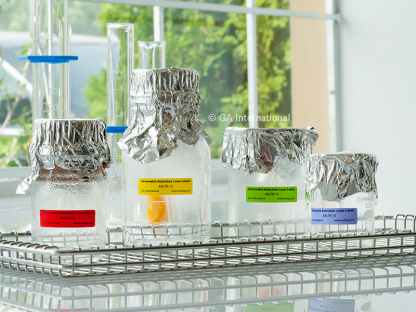 Various glassware on a metal rack, following a steam autoclave cycle, labeled with different color removable autoclave resistant laser labels.