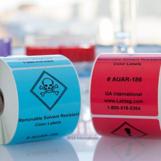 Eine Rolle hellblauer und eine Rolle roter lösungsmittelbeständiger, entfernbarer Farbetiketten zur Verwendung auf Behältern mit Lösungsmitteln und Chemikalien auf einem Labortisch.