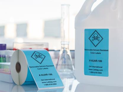 Auf einem Labortisch eine Rolle hellblauer lösungsmittelbeständiger Etiketten und ein AUAR-Farbetikett, die an einer Lösungsmittelflasche aus Kunststoff befestigt sind