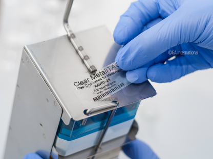 A researcher is sticking a clear MetaliTag label to a metal rack intended to go in liquid nitrogen. The label is printed with information and a barcode
