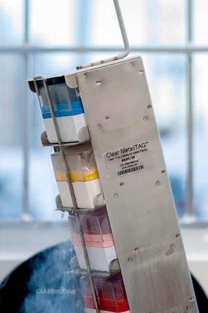 A vertical metal rack filled with cryo boxes is being held in the air, labeled with a clear cryogenic resistant MetaliTag label on its side