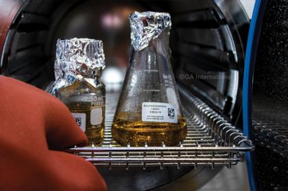 Eine Flasche und ein Kolben, die mit LabTAG-autoklavenbeständigen Ausblocketiketten gekennzeichnet sind, werden nach einem Sterilisationszyklus aus dem Autoklaven entfernt
