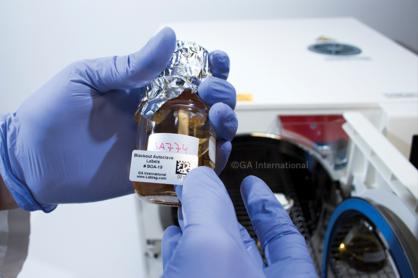 Ein autoklavenbeständiges Blockout-Etikett wird auf ein normales Etikett auf einer Glasflasche aufgebracht. Ein tragbarer Autoklav ist im Hintergrund