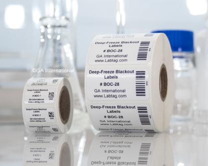 Zwei Rollen LabTAG-Tiefkühl-Blackout-Etiketten in verschiedenen Größen, die nebeneinander mit Text und Barcode auf einem Labortisch gedruckt sind.