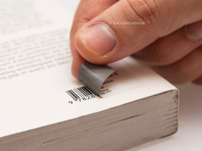 A hand applying a printed paper thermal-transfer blackout label on a book to cover-up the existing 1D barcode.