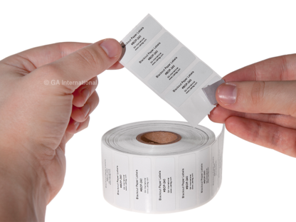 A hand peeling a blackout paper label from its liner, above a roll of thermal-transfer printed cover-up paper labels, on a table.