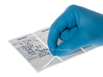 A gloved hand lifting the laminate from a writable self-laminating calibration label for reagents, on which relevant information has been written.