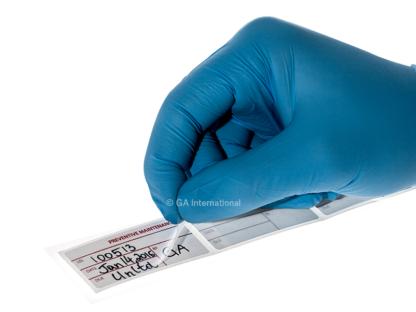 Eine behandschuhte Hand, die das Laminat zur vorbeugenden Wartung von einem beschreibbaren selbstlaminierenden Kalibrierungsetikett abhebt und mit relevanten Informationen versehen ist.