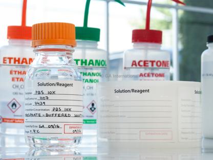 Eine Glasflasche, die mit einem selbstlaminierenden Kalibrierungsetikett versehen ist, das die Lösung / das Reagenz im Inneren identifiziert. Ein leeres Etikett steht daneben.