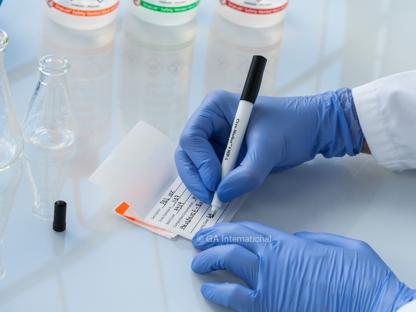 Ein Forscher mit blauen Handschuhen, der auf ein selbstlaminierendes Kalibrierungsetikett mit einem schwarzen permanenten Kryo-Marker schreibt.