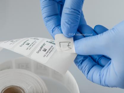 Eine Rolle von Tiefkühletiketten mit einer RFID-Antenne, die mit Informationen und Barcodes bedruckt ist. Eine Hand löst das erste Etikett vom Träger.