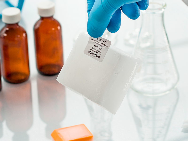 A gloved hand holding a paraffin wax block suspended from a thermal-transfer label with a strong permanent adhesive printed with text and a barcode.