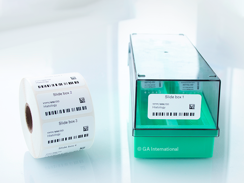 A roll of thermal-transfer printed labels, next to a slide storage box, labeled with a freezer-grade barcode label printed with 1D and 2D barcodes.