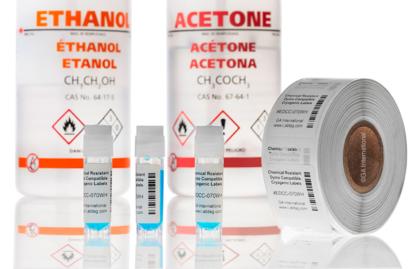 3-Kryo-Fläschchen mit chemikalienbeständigen, kryogenen DYMO-kompatiblen Etiketten neben einer Etikettenrolle und vor Flaschen mit Ethanol und Aceton.