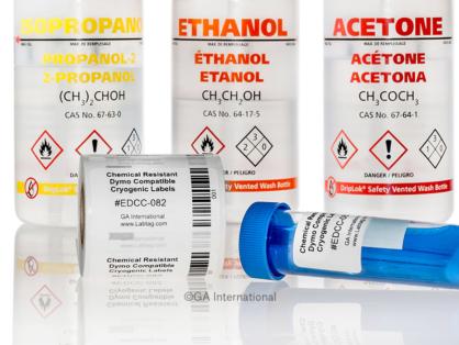 Beschriftetes 50 ml-Röhrchen neben einer Rolle DYMO-kompatibler, chemikalienbeständiger Kryo-Etiketten. Flaschen Isopropanol, Ethanol und Aceton im Hintergrund.