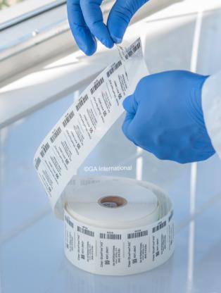 Eine Rolle transparenter, klebstofffreier, statisch haftender Etiketten befindet sich auf einer Labortheke. Eine Hand entfernt eines der vorgedruckten Etiketten.