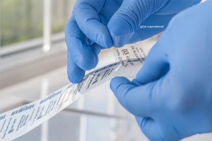 Ein transparentes, klebstofffreies Etikett, das mit 1D- und 2D-Barcodes bedruckt ist, wird von seiner Rückseite gelöst.