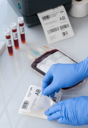 Hand removing secondary blood bag label from its liner. Next to blood collection tubes, a full blood bag and a thermal-transfer printer.