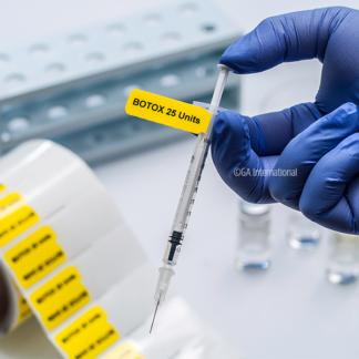 Eine behandschuhte Hand mit einer Spritze, die mit einem vorgedruckten Spritzenetikett versehen ist und den Inhalt der Spritze als 25-Einheiten von Botox angibt.