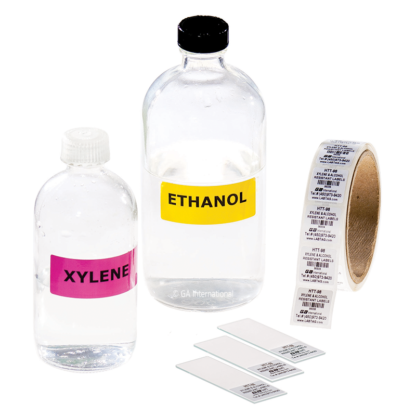 Two printed rolls of xylene and chemical resistant labels, next to three labeled slides, and cassettes, and a glass bottle containing xylene.