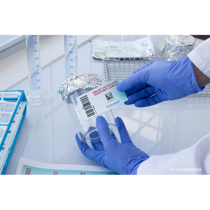 A gloved hand labeling a glass beaker with an inkjet printable autoclave resistant label, printed with alphanumeric text and a 2D barcode.
