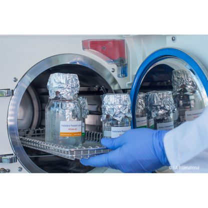 A gloved hand removing a metal rack from a steam autoclave, with glassware labeled with autoclave resistant color printed inkjet labels.