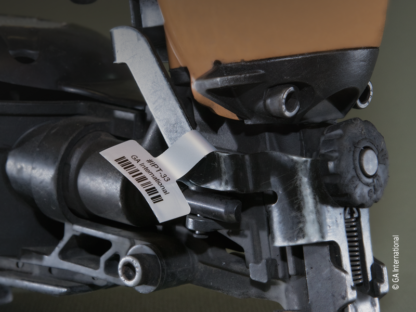 A nail gun labeled with a silver thermal-transfer industrial price tag, by GA international, printed with alphanumeric text and a 1D barcode.