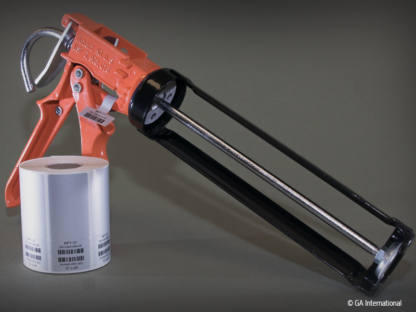 A silicone gun labeled with a silver thermal-transfer industrial price tag, printed with alphanumeric text and a 1D barcode, next to a printed roll.