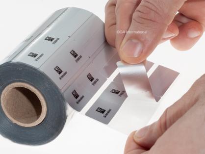 Eine Hand, die ein Etikett von einer mit Barcode bedruckten Rolle aus doppelseitigem Silberschmuck und optischen Rattenschwanzetiketten von GA International entfernt.