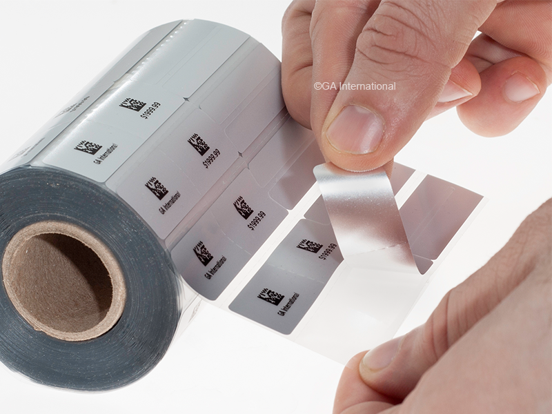 ea26f5cf5d51 A hand removing a label from a barcode printed roll of double-sided silver  jewelry
