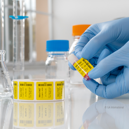 A yellow NitroTAG permanent cryogenic label being applied to a cryo vial, next to a roll of printed cryogenic barcode labels on a lab table.