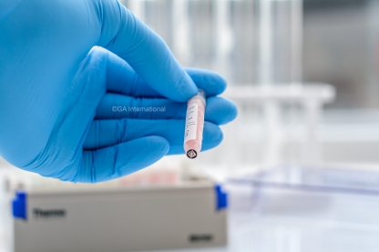 A researcher is holding a frozen matrix tube labeled with a cryo-resistant label, and with a 2D barcode printed label on the bottom of the tube.