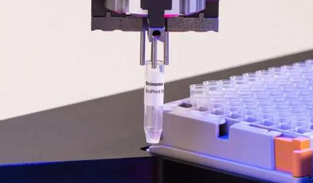 Der automatisierte Scinomix RETROS-Arm eines automatisierten Röhrchenetikettierers mit einem etikettierten Reagenzglas, entnommen von einem Arbeitsdeck mit vollem Rack mit 96-Röhrchen.