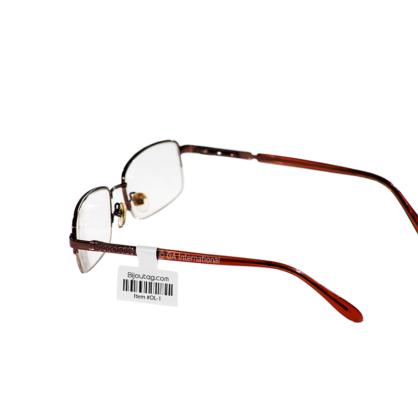 Mit einem Thermotransferetikett für optische Rahmen von GA International beschriftete Brillen, die mit alphanumerischem Text und einem 1D-Barcode bedruckt sind.