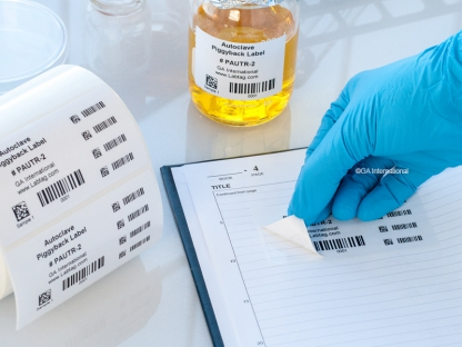 A gloved hand applying a piggyback label to a notebook, next to a roll of removable autoclave-resistant piggyback labels and a labeled bottle.