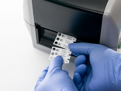 A scientist wearing blue gloves cutting-off three strips of PCR-TagTrax, tags for High-profile PCR tubes, printed with text and a 2D barcode.