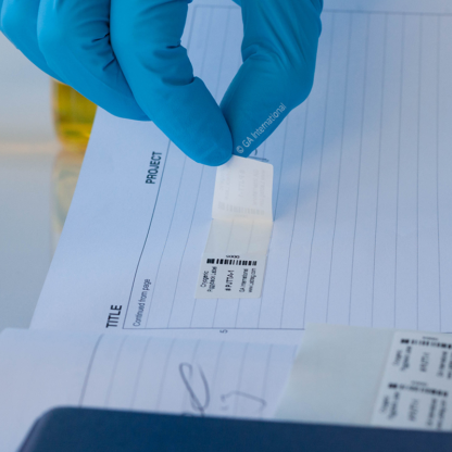A gloved hand peeling-off a secondary label from a barcode printed cryogenic piggyback thermal-transfer label placed in a lab notebook.
