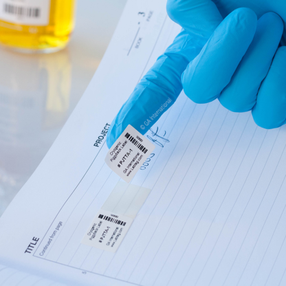 A gloved hand holding a secondary label from a barcode printed cryogenic piggyback thermal-transfer label placed in a lab notebook.