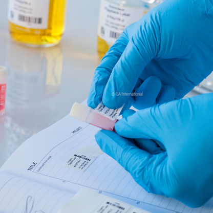A gloved hand applying a label to a cryo vial from a barcode printed cryogenic piggyback thermal-transfer label placed in a lab notebook.