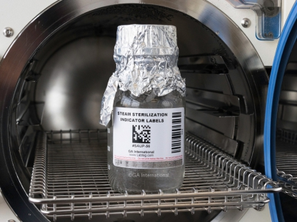 Glass bottle after autoclave cycle, labeled with a steam sterilization indicator barcode label, with the indicator strip turned charcoal grey.