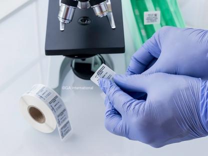 Eine behandschuhte Hand, die auf einem Objektträger neben einem Mikroskop und einer Etikettenrolle ein lösungsmittelbeständiges, entfernbares Verdunkelungsetikett über einem vorhandenen Etikett anbringt.