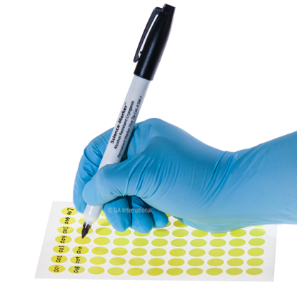 A gloved hand writing on small yellow dot labels using the Science-Marker, an alcohol and water resistant permanent black ink marker with a fine tip.