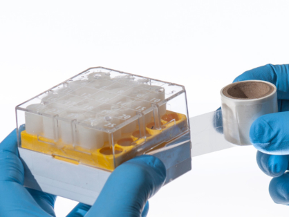 A gloved hand labeling an already frozen cryo box, containing cryo vials, with Clear CryoSTUCK, transparent cryogenic tape by LabTAG.
