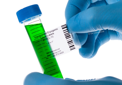 A gloved hand applying a clear removable cryogenic laser label to a 15 ml tube filled with a green liquid. The label is printed with text and a barcode.