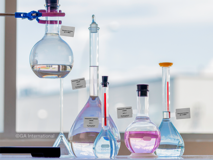 Group of various volumetric flasks labeled with thermal-transfer volumetric labware labels, printed with alphanumeric text.