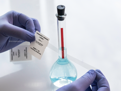 A gloved hand applying a volumetric labware label to a glass volumetric flask filled with a light blue liquid. Label printed with standard information.